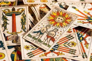 Crop view of many tarot cards disorderly lying on table with one with the sun and Le Soleil sign on top